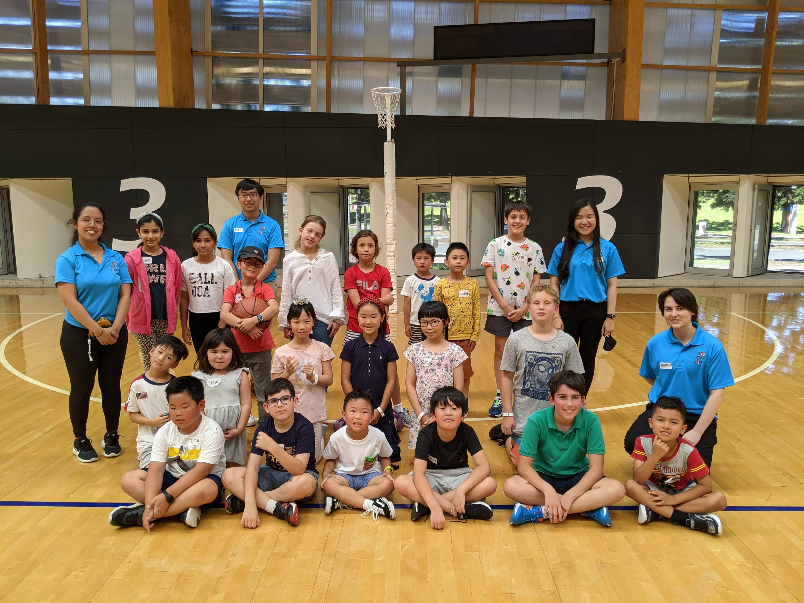 Group of PIEX kids and teachers in a basketball court