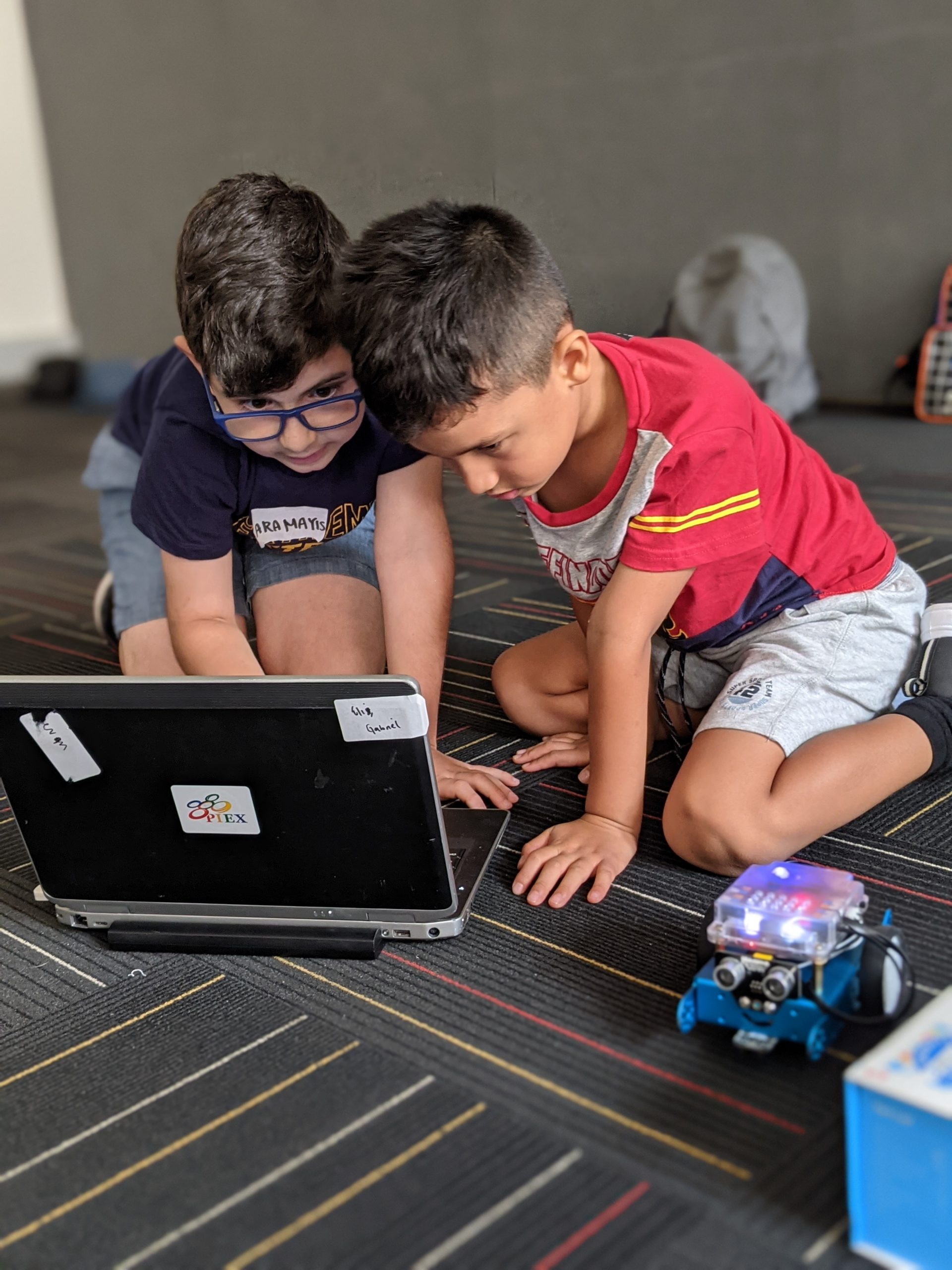 Two Boys WOrking on the laptop to control their educational robot, mBot.